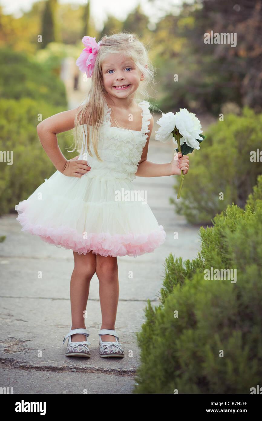 37d8dd1f336f9 Des yeux d un bleu profond incroyable enfant bébé fille habillée élégante  robe rose coloré avec des cheveux blonds brillant et blanc sandales posant  pour ...