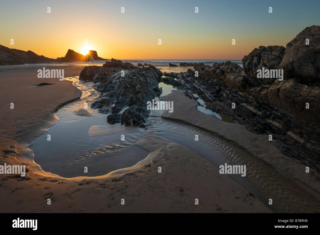 Pierres et piscine dans les rochers sur la plage à marée basse au coucher du soleil, Zambujeira do Mar, de l'Alentejo, Portugal, Europe Photo Stock