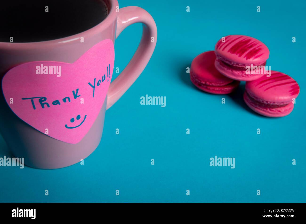 Tasse à café et macarons roses sur fond bleu. Note papier avec un message de remerciement fixés sur la tasse de café Photo Stock