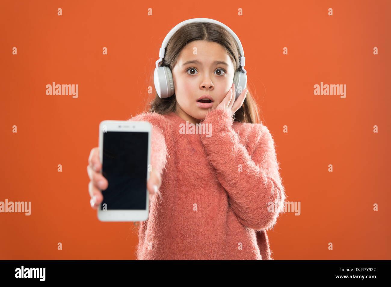 La version de l'application obsolète. Best free apps de musique. Ecoutez gratuitement. Obtenir de la musique compte abonnement. Profitez de la musique concept. Profitez d'un son parfait. Petite fille musique écouter casque moderne et smartphone. Photo Stock