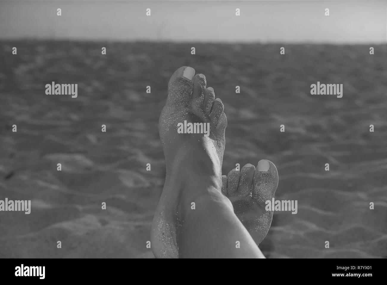 Une photo d'une femme se prélasser à la plage Banque D'Images