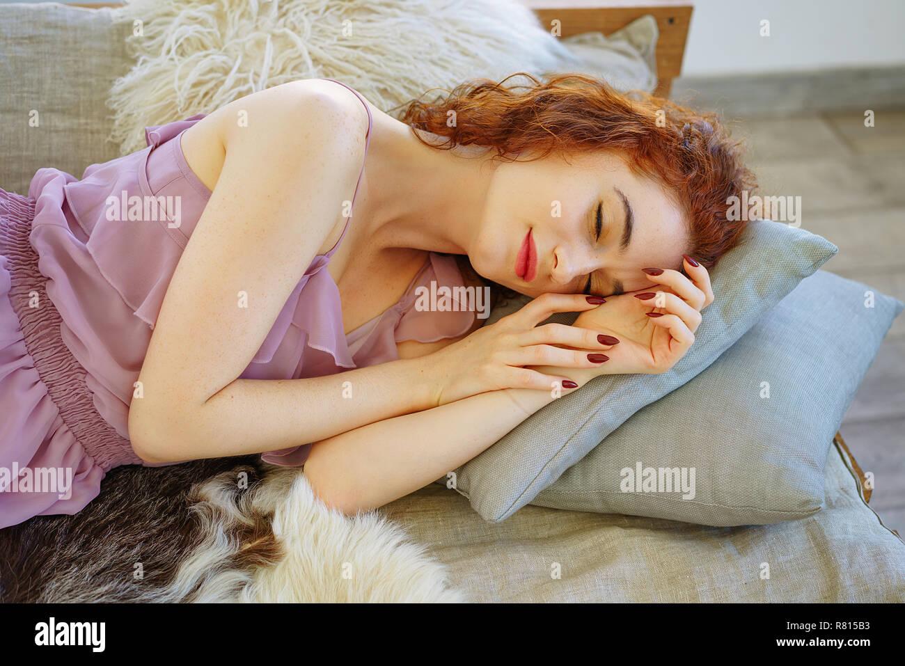 Belle jeune femme aux cheveux rouges sur le divan. Banque D'Images