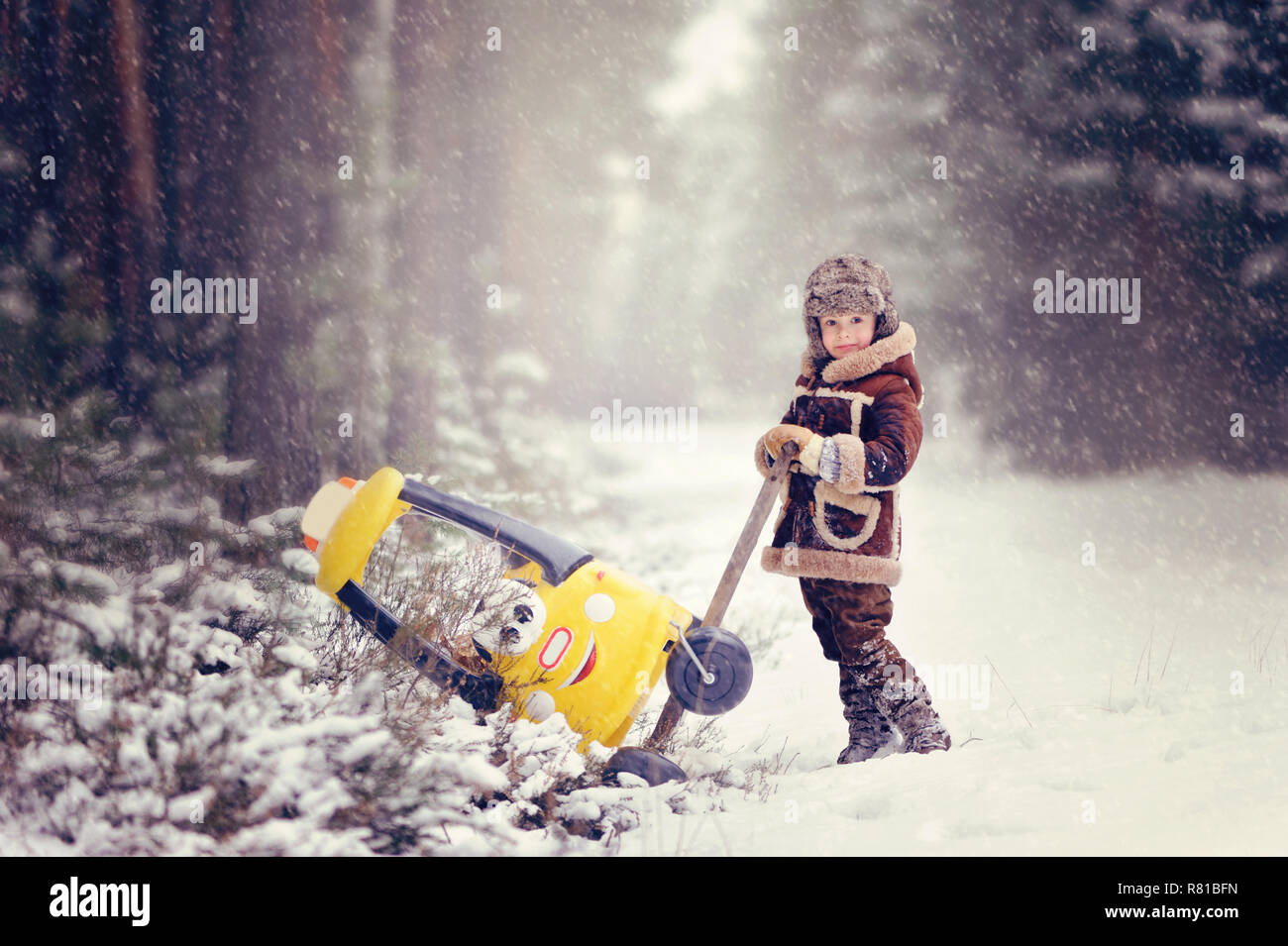 Enfant jouant à l'extérieur au cours de neige. Le garçon pousse de la neige petite voiture jaune, avec deux ours en peluche à l'intérieur, belle hiver neigeux par Banque D'Images