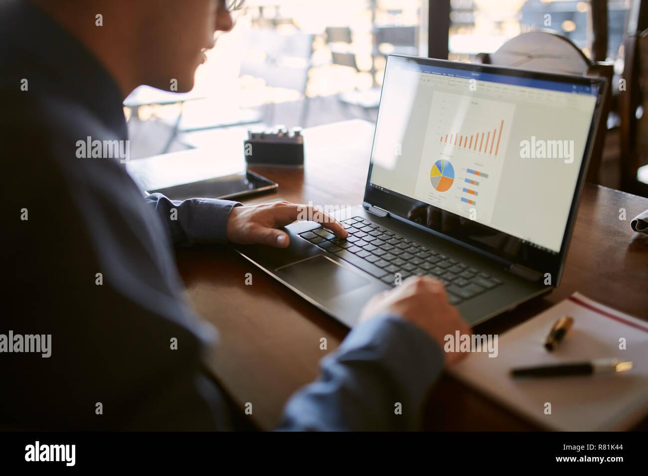 Close-up vue arrière de caucasian businessman hands typing on laptop clavier et pavé tactile à l'aide. Carnet et un stylo sur le premier plan de l'espace de travail. Des tableaux et des diagrammes à l'écran. Pas de visage isolé vue. Photo Stock
