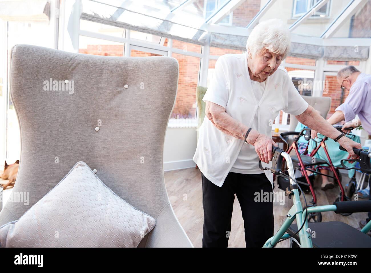 Senior Woman Using aide à la mobilité dans le salon de la maison de retraite Photo Stock