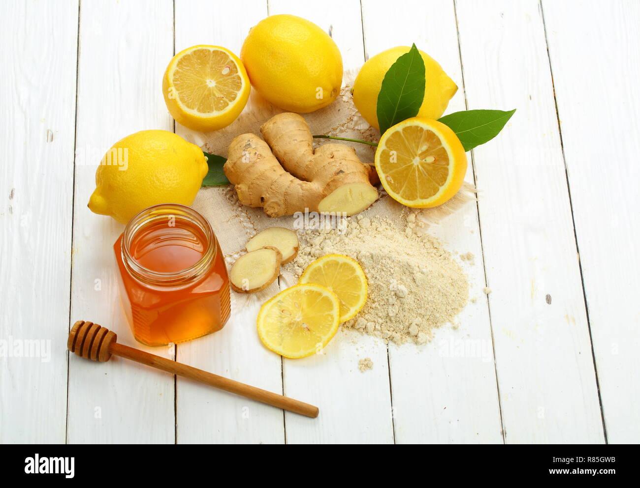 Racine de gingembre, citron et miel sur fond de bois blanc Banque D'Images
