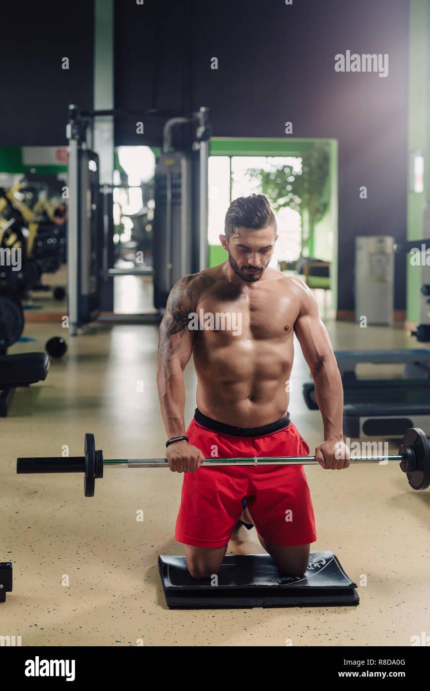 Homme fort dans la salle de sport faire des exercices d'épaule Photo Stock