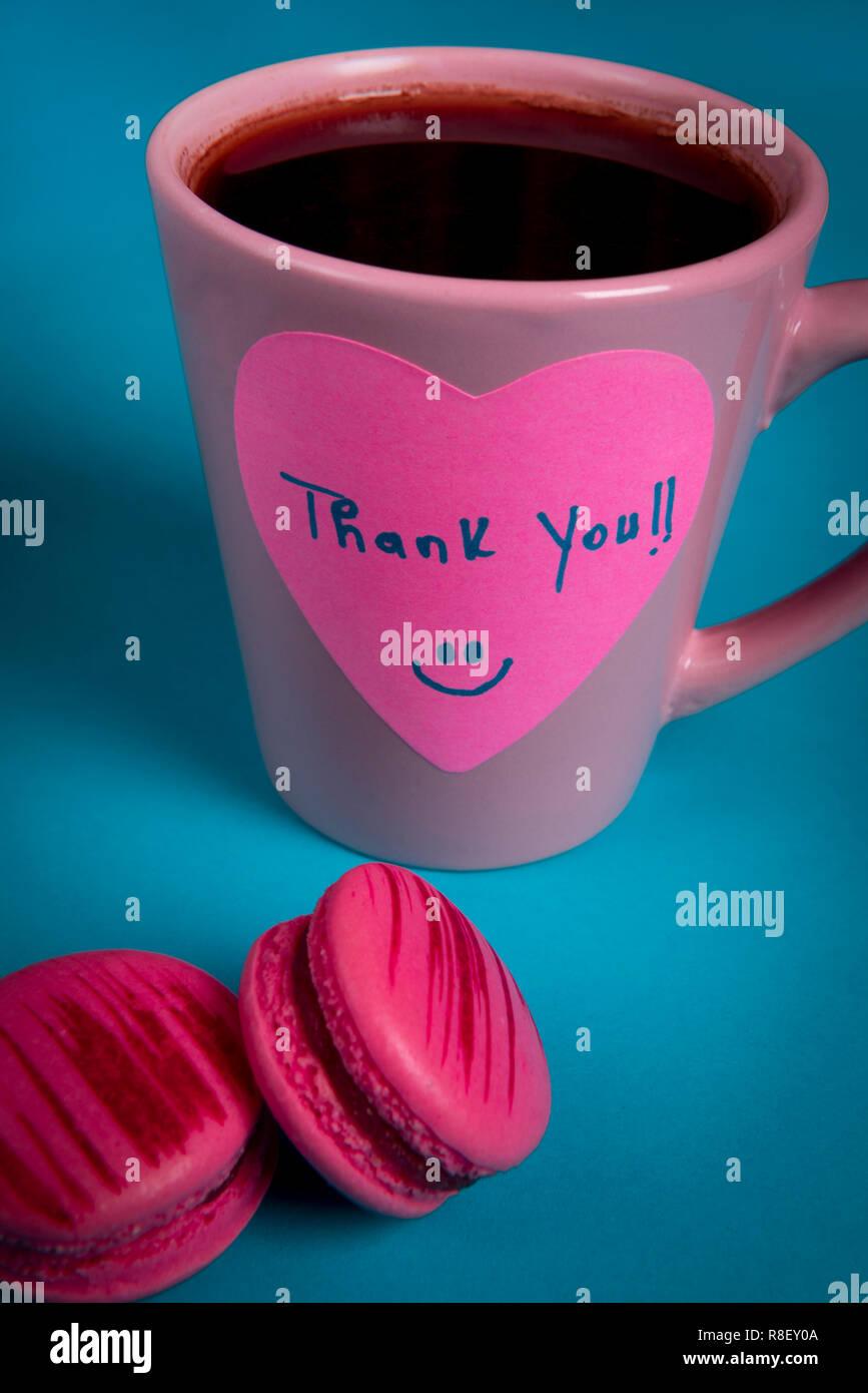 Message de remerciement à la main sur un post-it en forme de cœur. Tasse de café rose et deux macarons rose sur un tableau bleu Photo Stock