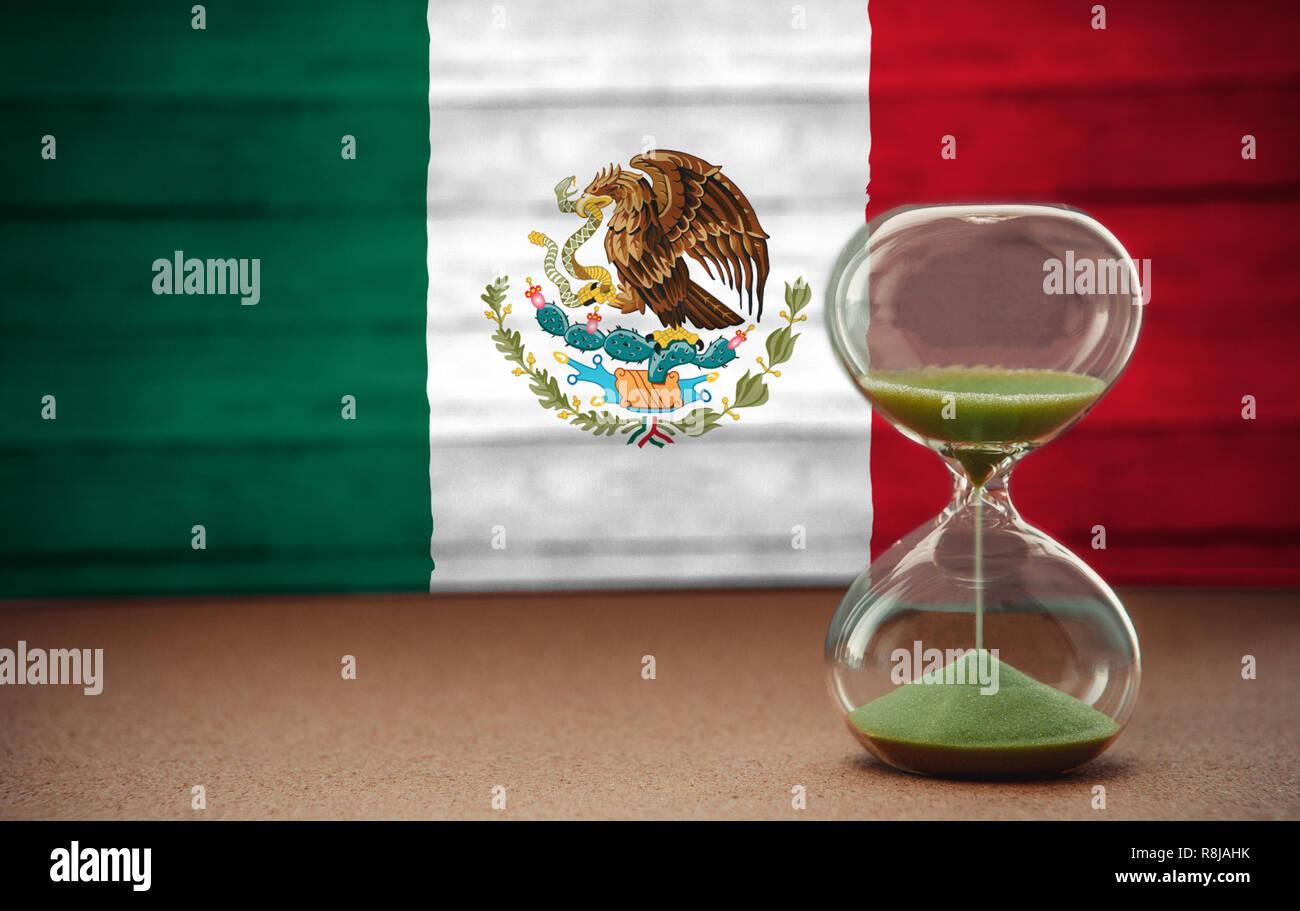 Le sable dans les vases du sablier mesurant le temps qui passe dans un compte à rebours jusqu'à une date limite, sur fond du drapeau mexique with copy space Banque D'Images