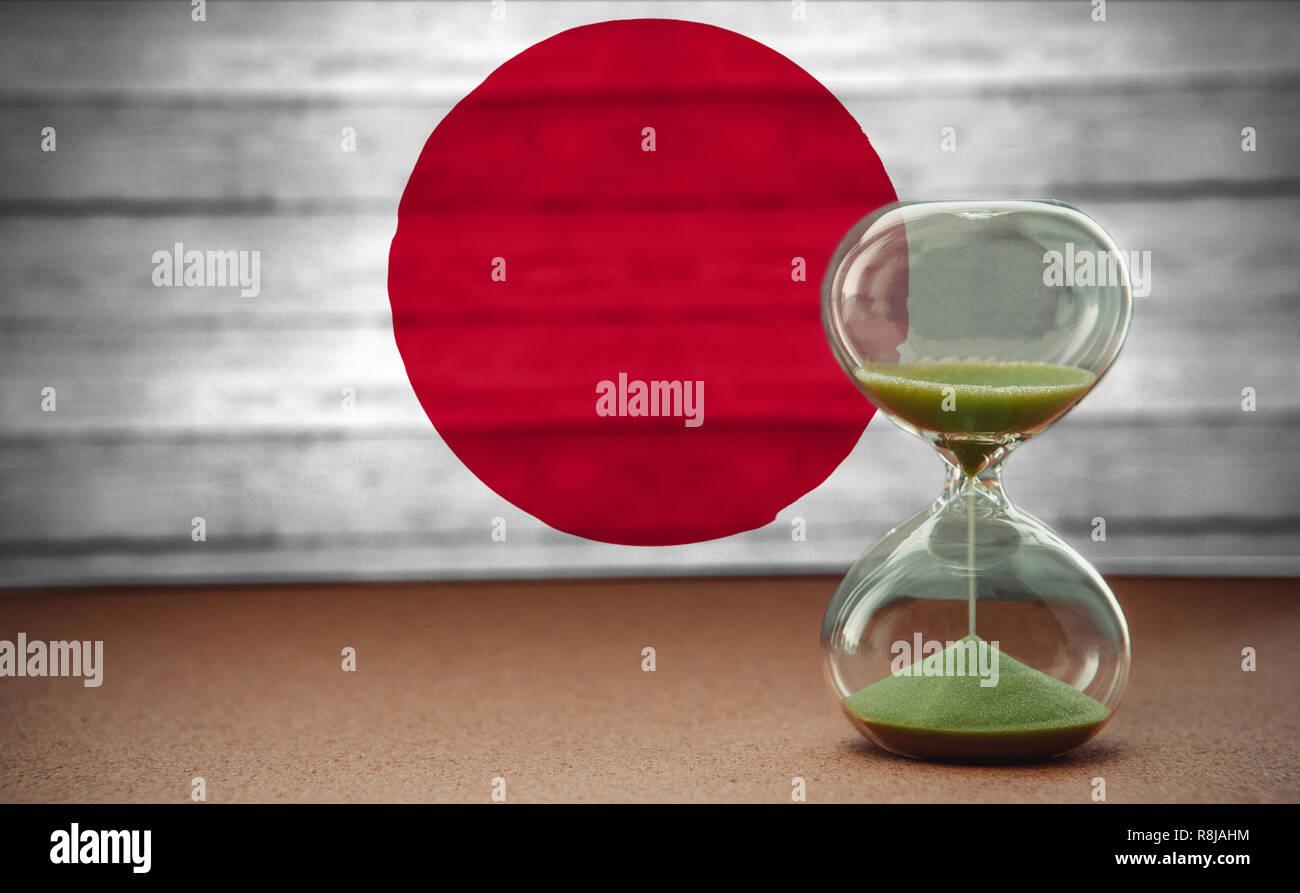 Le sable dans les vases du sablier mesurant le temps qui passe dans un compte à rebours jusqu'à une date limite, sur fond du drapeau Japon with copy space Banque D'Images