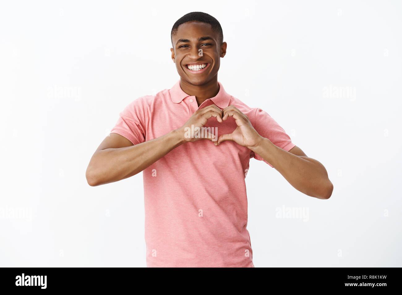 Wais-plan de nature sincère et mignon jeune homme afro-américain d'amour et de partage de tendres sentiments montrant un large sourire et geste du cœur en confessant notre sympathie à mère sur mur blanc Photo Stock