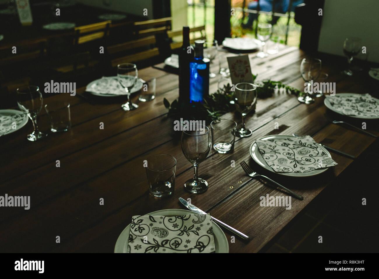 Tables en bois avec des couverts et assiettes verres rétroéclairé sans que personne. Photo Stock
