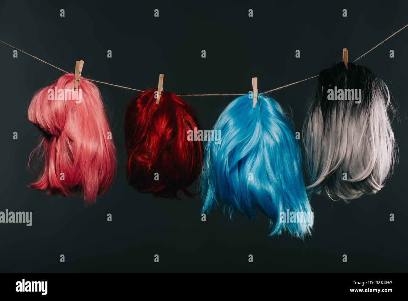 Quatre perruques colorées pendaison sur corde isolated on black Photo Stock