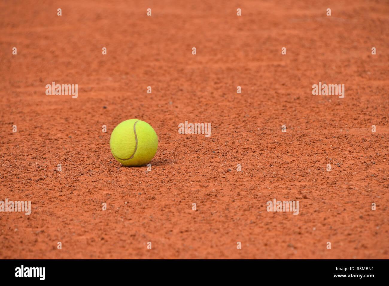Près d'un feutre jaune balle de tennis sur un sol argileux brun rouge court, low angle view Banque D'Images