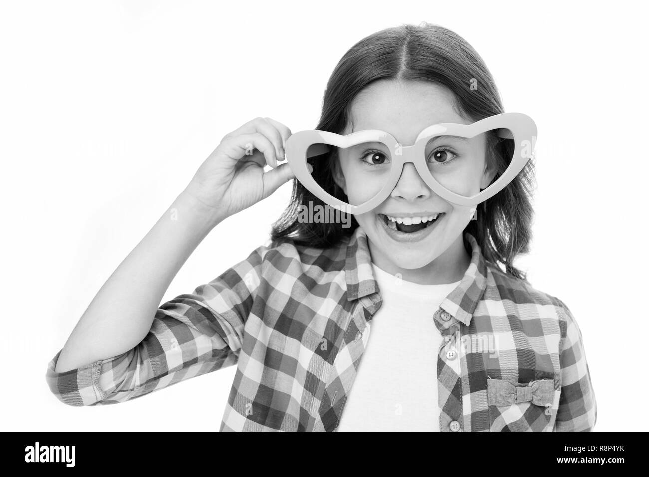 Sweet l'enfance. Happy Kid se sent belle sympathie. Charmant sourire de l'enfant isolé sur fond blanc. Les lunettes en forme de coeur fille célèbre le Jour de Valentines. Adorable fille lunettes coeur visage souriant. Photo Stock