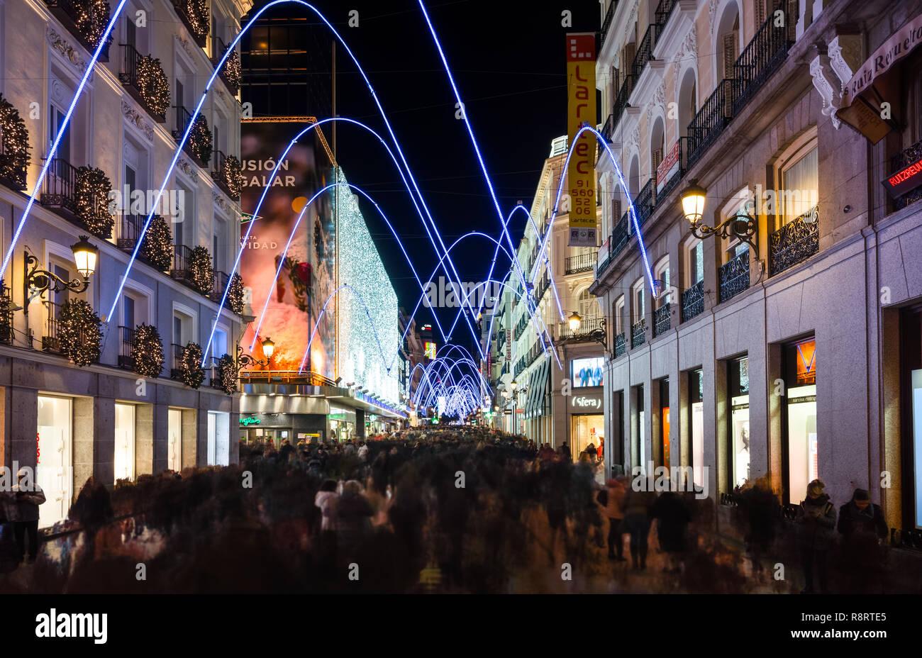 Madrid, Espagne, décembre 2018. Les gens qui marchent et des magasins à la tombée de la rue Preciados, éclairé par des lumières de Noël. Photo Stock
