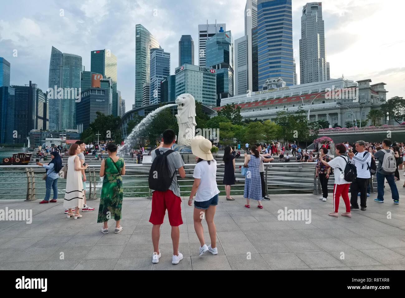 Les touristes asiatiques s'assemblant autour du Merlion, la moitié-moitié de poisson-lion statue, au Parc Merlion, Singapour; zone.: le quartier des banques & Fullerton Hotel Banque D'Images
