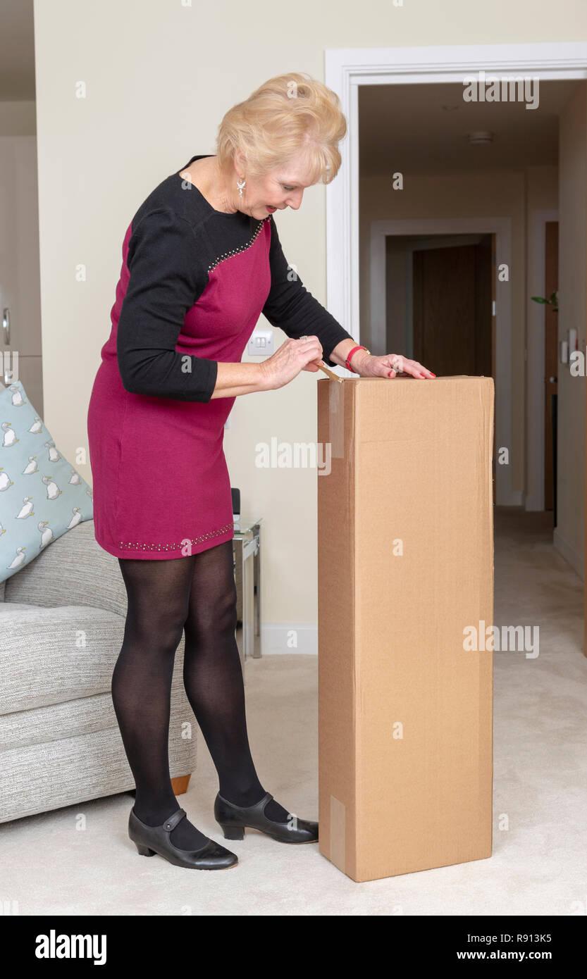 Femme de l'ouverture d'une boîte en carton brun livré par messagerie Photo Stock