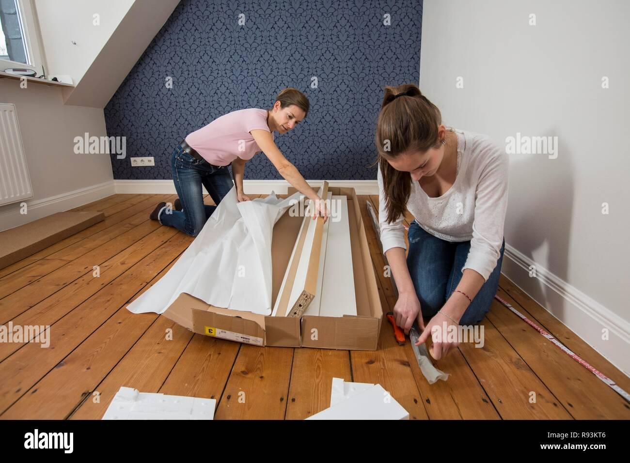 Mère et fille qui travaille ensemble pour former un lit double dans la chambre, lit fille jeux de montage, Allemagne Photo Stock