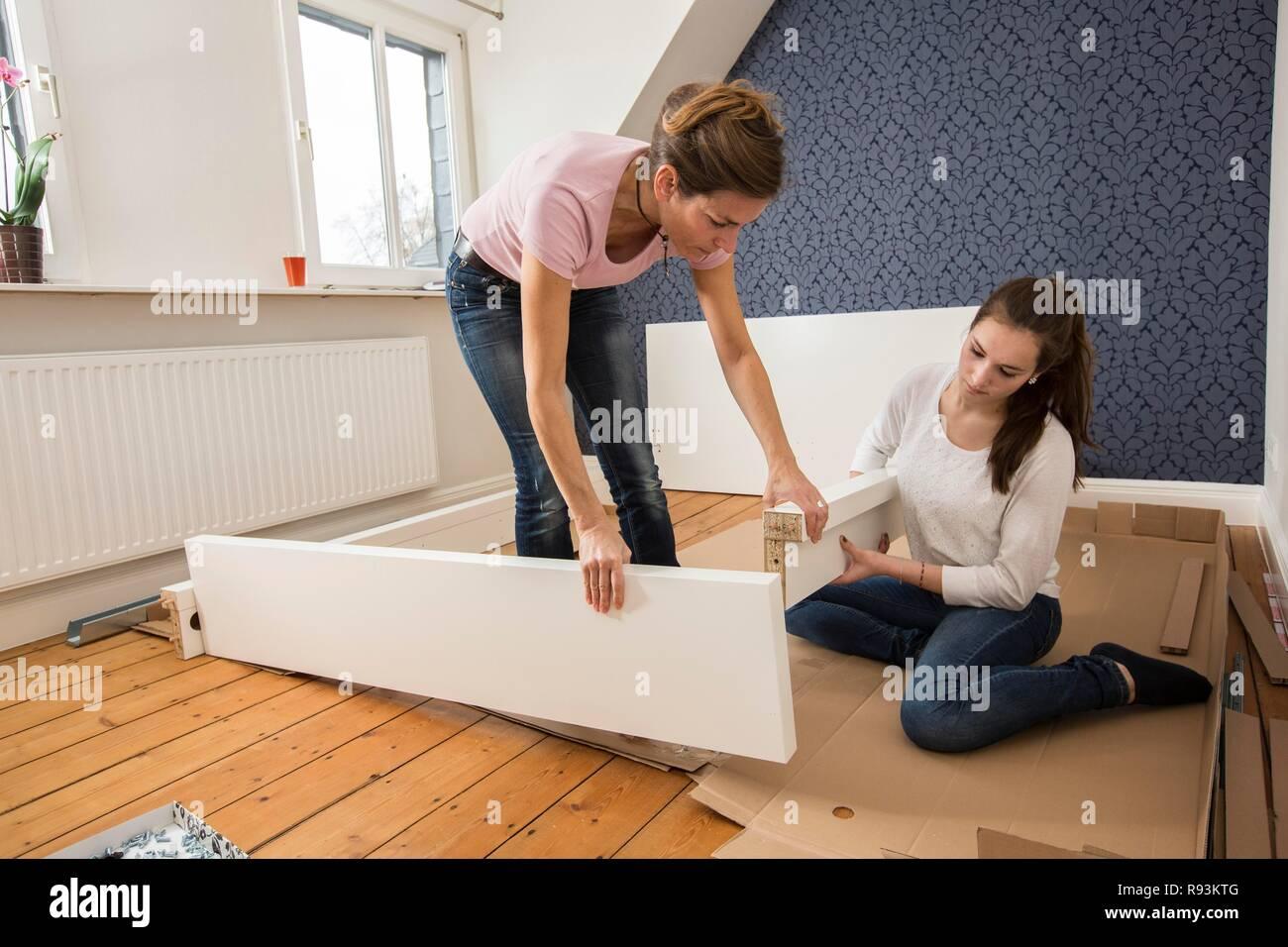 Mère et fille qui travaille ensemble pour former un lit double dans ...