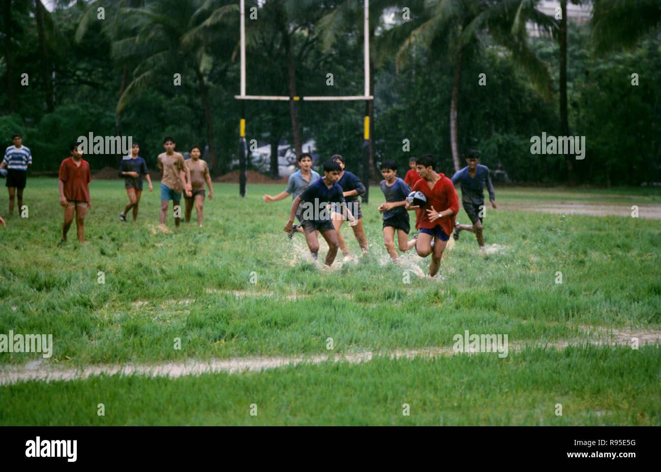 Jeunes garçons jouent au football américain dans la mousson, Bombay Mumbai, Maharashtra, Inde Photo Stock