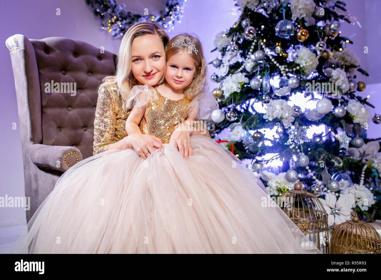 1348092a0ee3a Famille heureuse mère et fille en robe de luxe près de l'arbre de Noël. Air  de famille. Bonne Année et thème de Noël. Ambiance de fête.