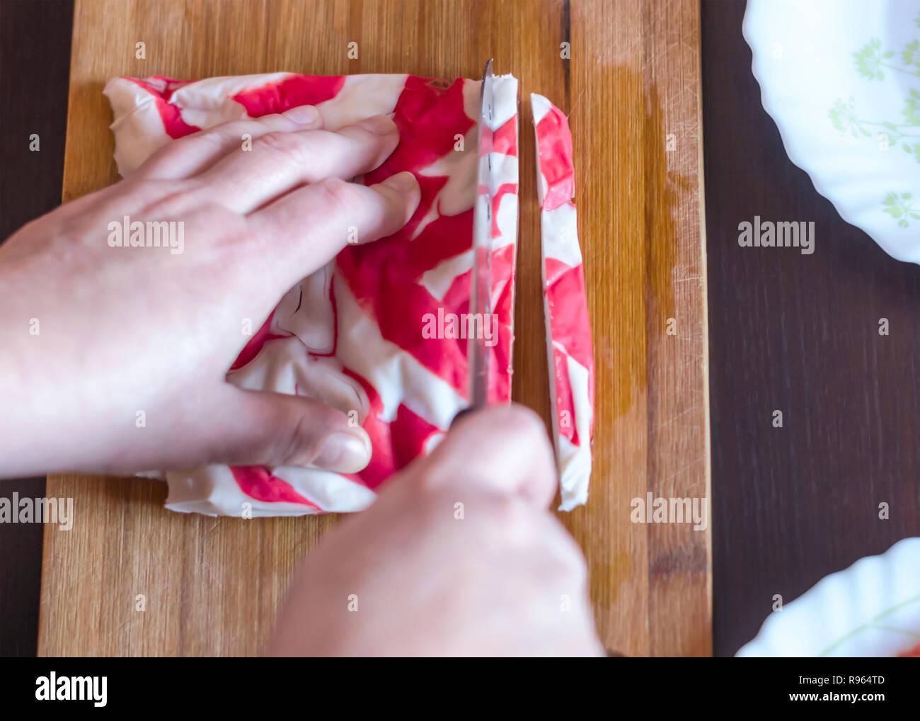 Crabe Avec Un Couteau woman's hands couper la chair de crabe kanikama ou couteau santoku