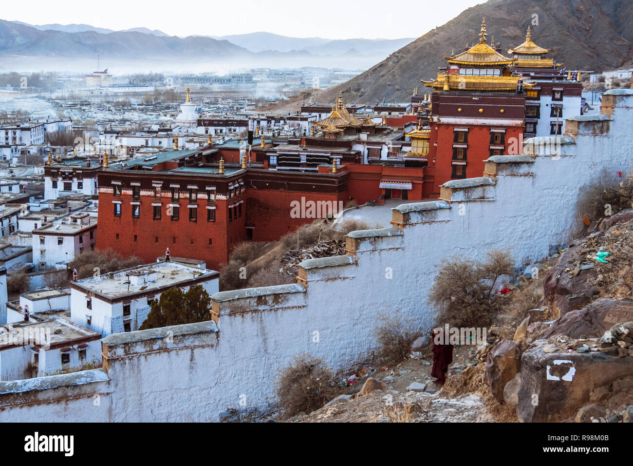 Shigatse, dans la région autonome du Tibet, Chine: un moine bouddhiste à pied à l'extérieur des murs du monastère de Tashi Lhunpo, siège traditionnel du Panchen Lama Photo Stock
