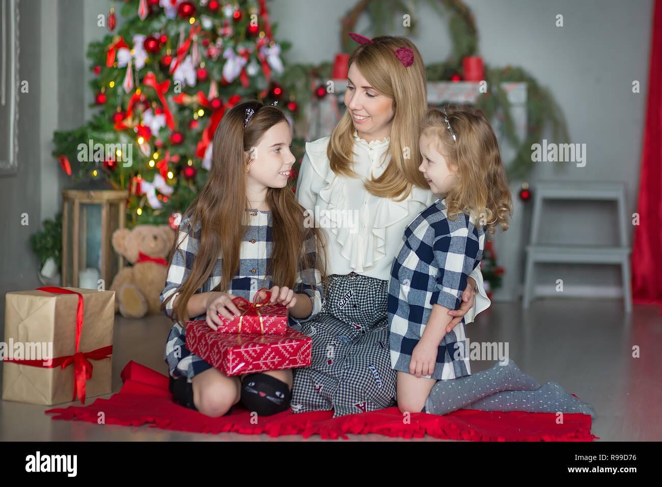 73ddb9ec63adf Super cute blonde mère mère de deux filles filles célébrant Noël Nouvel An  près d arbre de Noël pleine de jouets dans l élégant quartier de robes avec  des ...