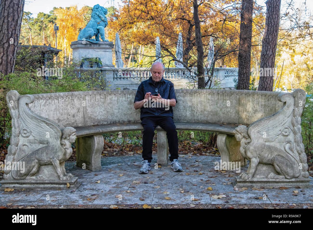 Berlin. Vieil homme est assis sur le banc en decorartive jardin de maison de la Conférence de Wannsee Memorial Site avec Lion Flensburg en arrière-plan.. Banque D'Images
