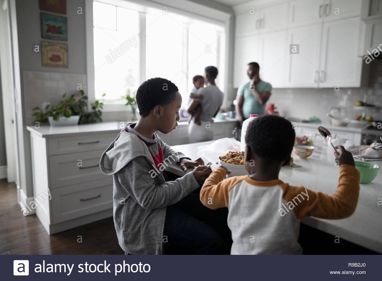 Frères manger des céréales à l'île de cuisine Photo Stock