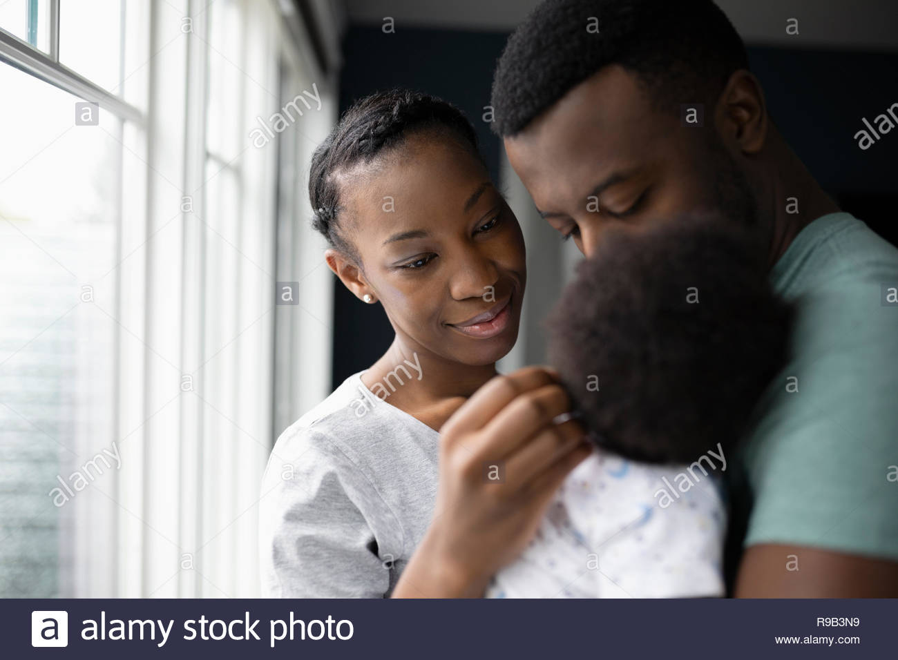 Affectionate couple holding baby son Banque D'Images