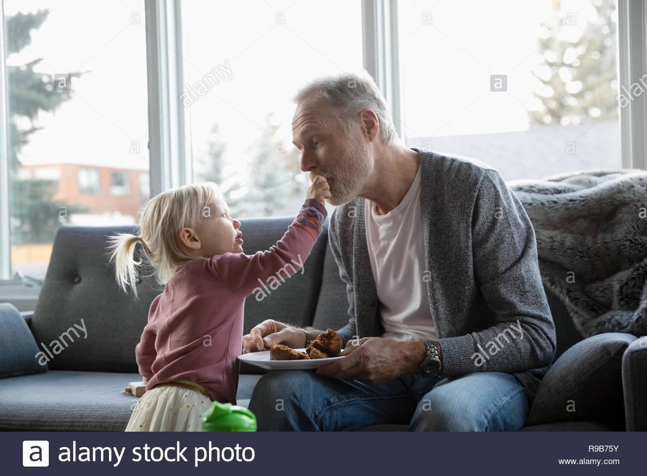 Petite-fille adorable grand-père d'un muffin en salon canapé Photo Stock