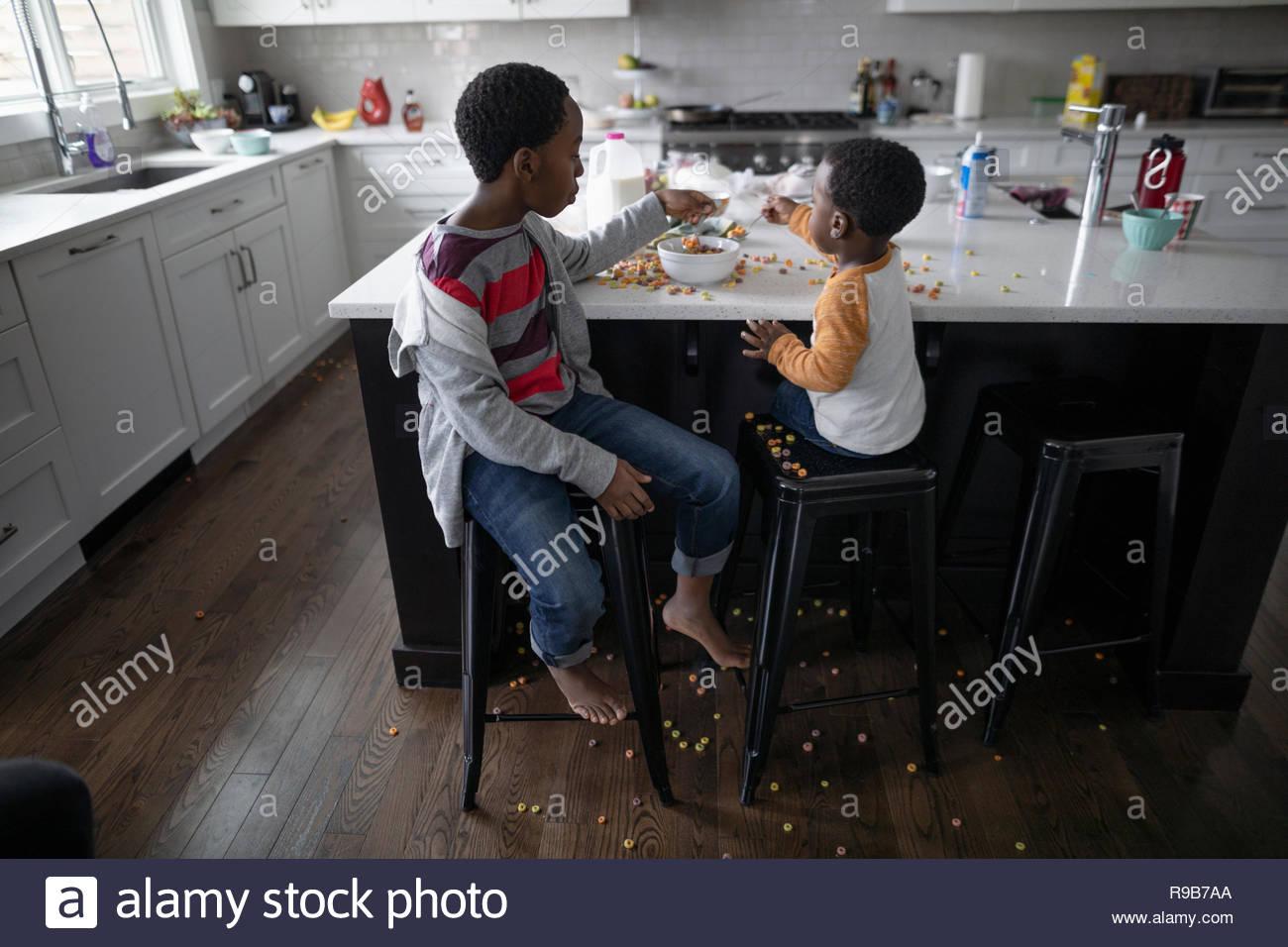 Frères malpropre manger des céréales à l'île de cuisine Photo Stock