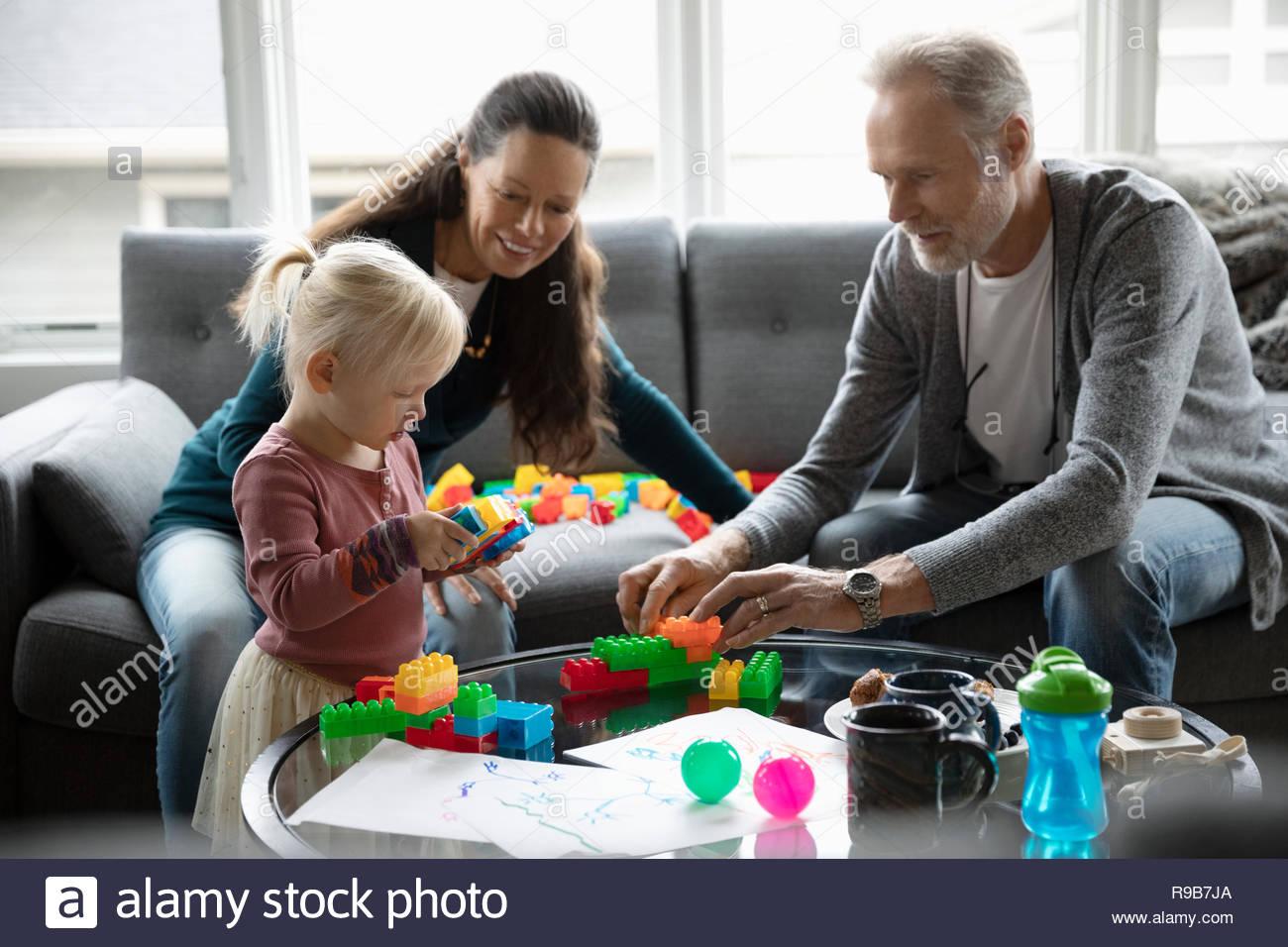Les grands-parents et sa petite-fille jouant avec des blocs en plastique dans la salle de séjour Photo Stock