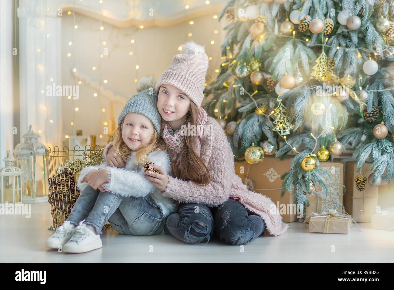 ac462e277e4f8 Deux filles super mignonnes sœurs célébrant Noël Nouvel An près d arbre de  Noël pleine de jouets dans l élégant quartier de robes avec des bonbons.