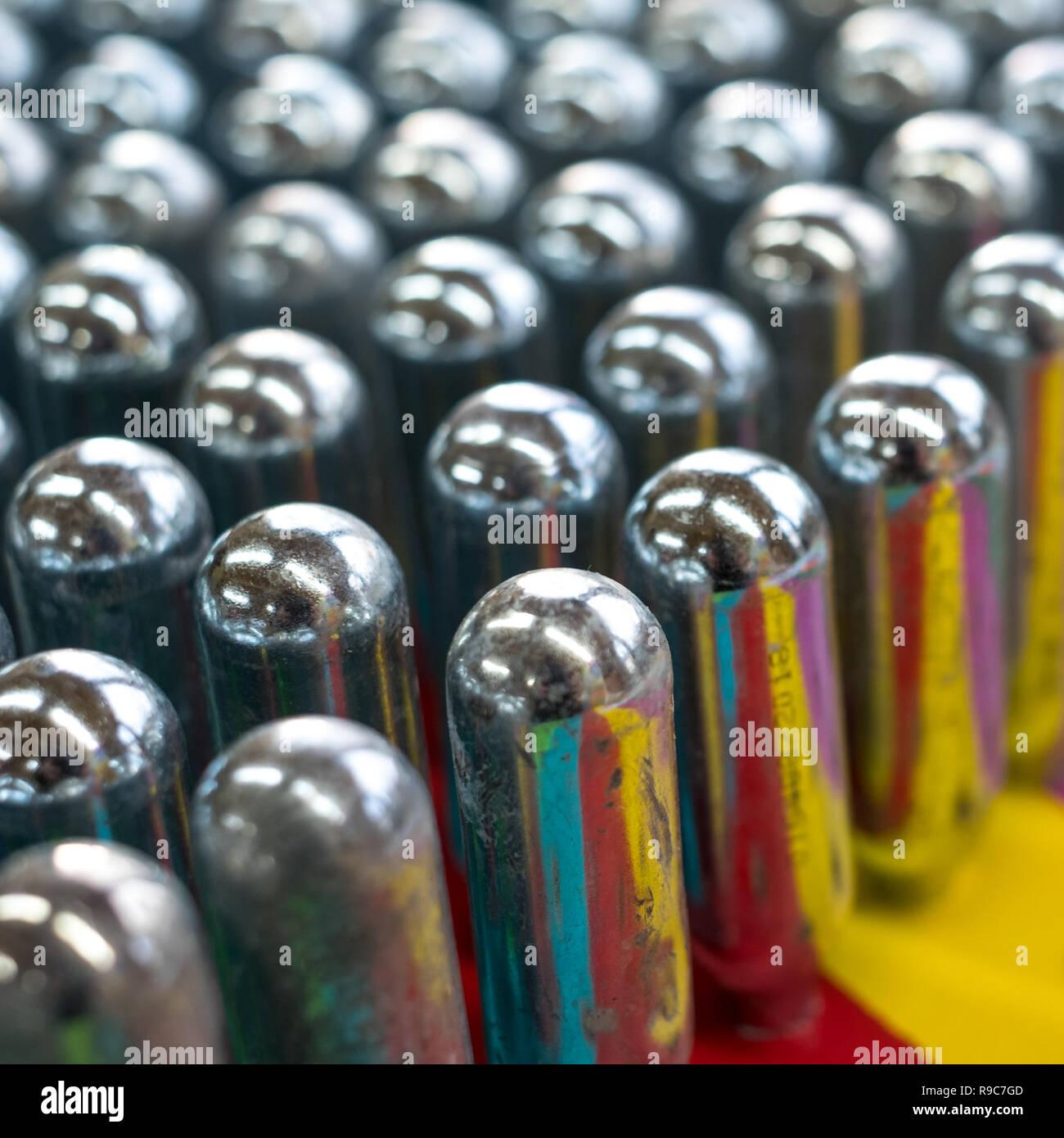 L'oxyde nitreux cannisters vide reflétant couleurs psychédéliques: cylindres de métal contenant de l'oxyde nitreux, utilisé pour la crème à fouetter, mais aussi comme un cadre juridique Banque D'Images