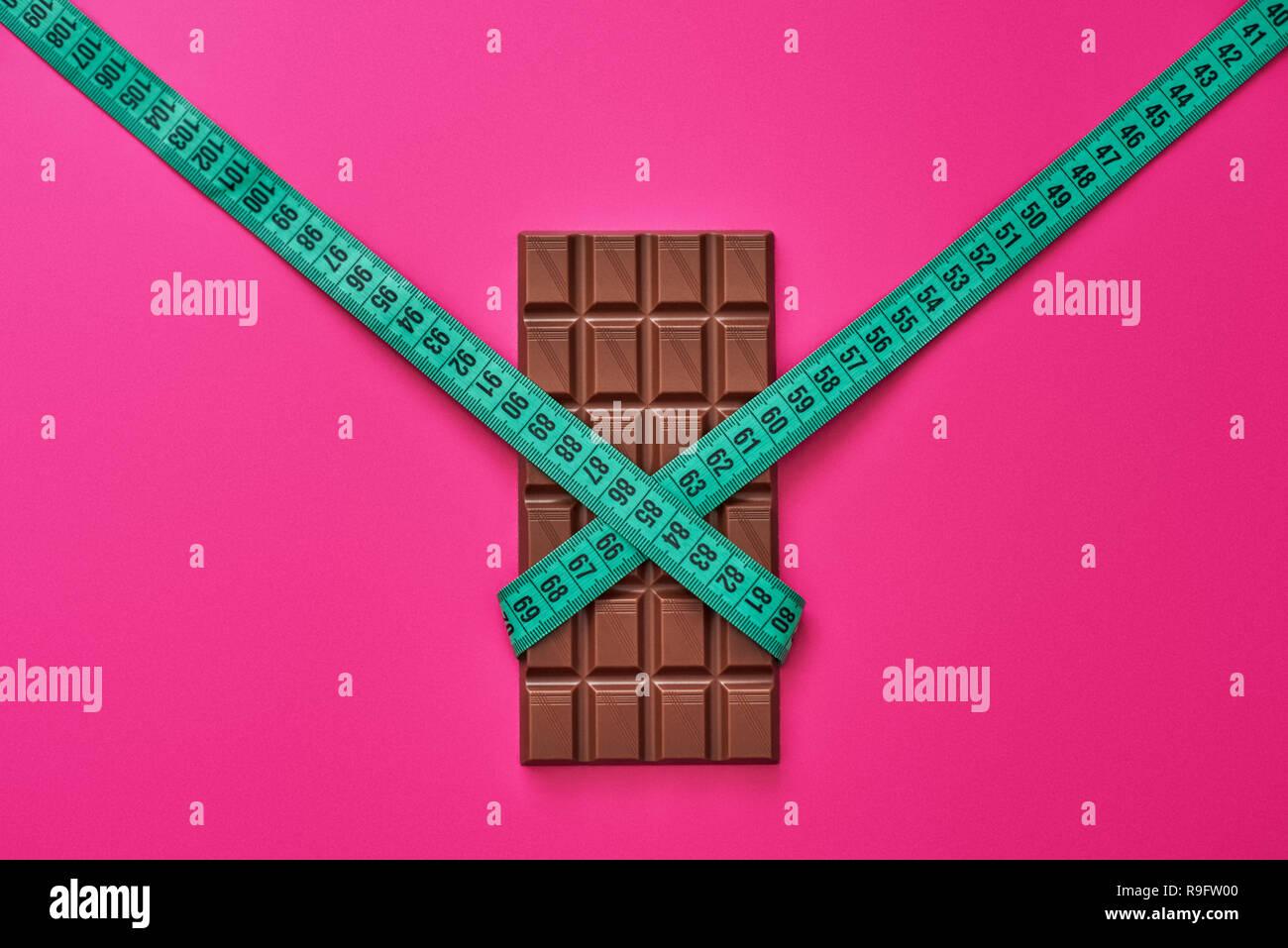 Résister aux tentations. Barre de chocolat emballés avec du ruban de mesure isolé sur fond rose Photo Stock