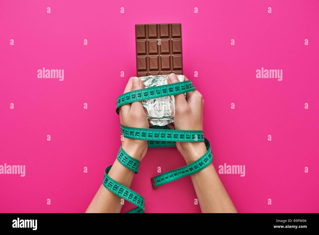 Oubliez pas de bonbons. Barre de chocolat dans les mains de womans emballés avec du ruban de mesure isolé sur fond rose. Suivre un régime alimentaire sain et concept Photo Stock