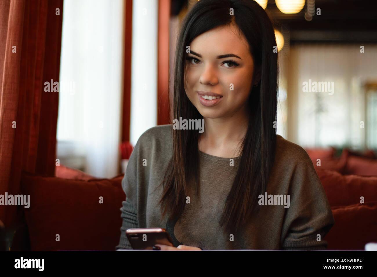Une belle fille avec les fossettes sur les joues dans un café confortable contre la fenêtre et bokeh. modèle attrayant détient le téléphone Banque D'Images