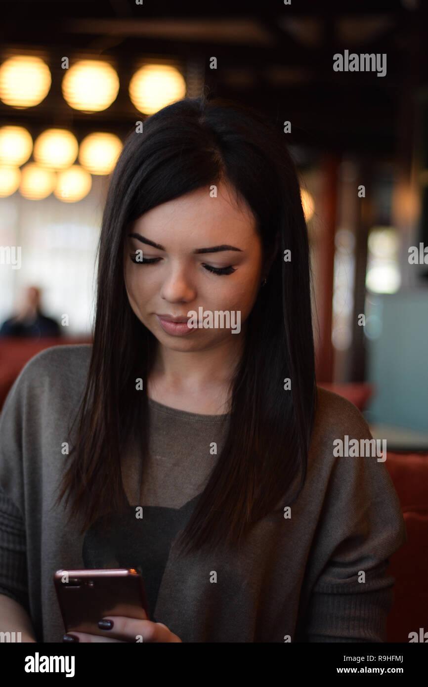 Portrait of a smiling belle fille avec des fossettes sur les joues dans un café confortable contre la fenêtre et bokeh. jeune femme est en train de lire un message dans la p Banque D'Images