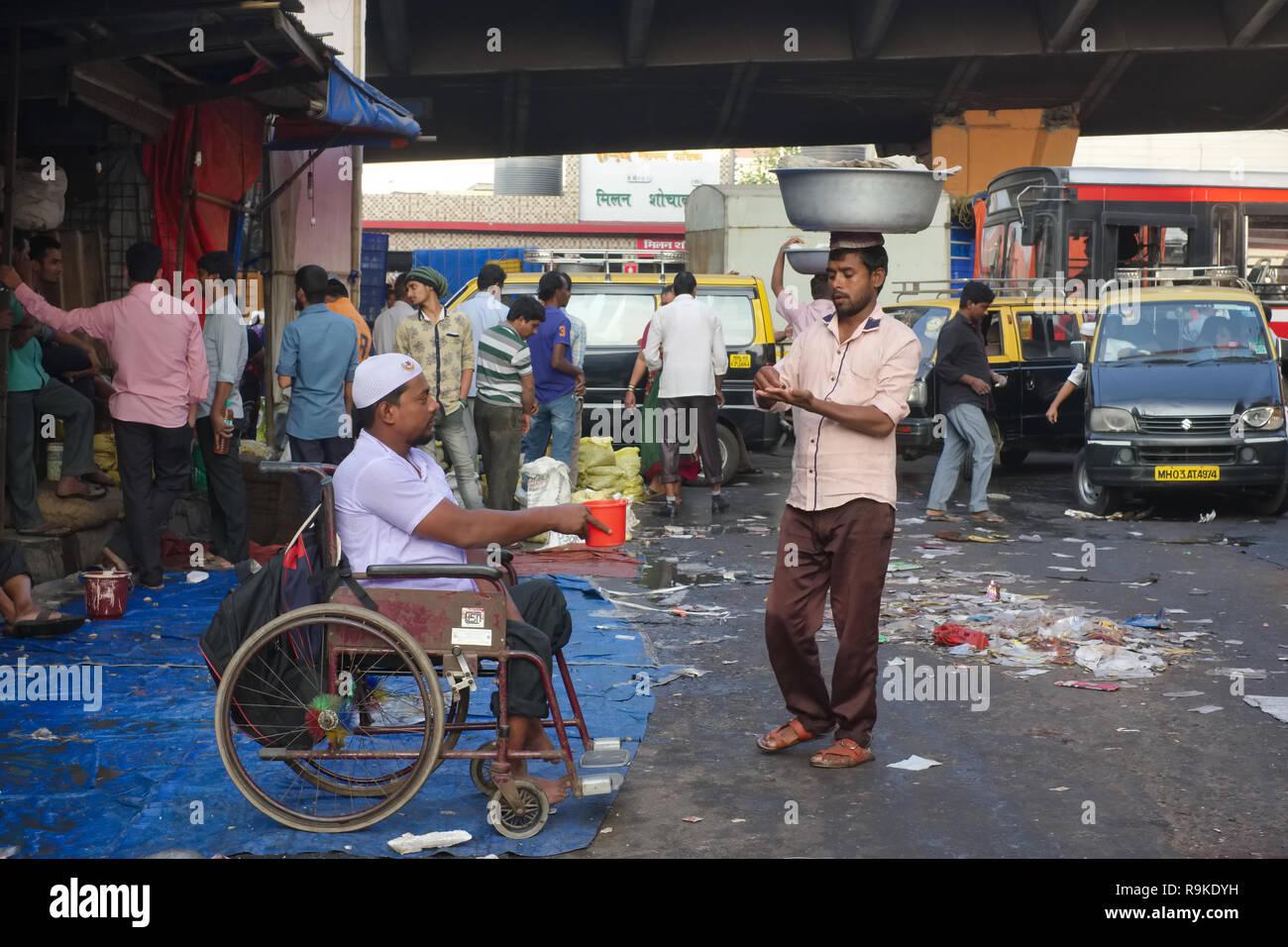 Un porteur dans un marché aux poissons à Mumbai, Inde, environ à part une petite somme d'argent à un mendiant Photo Stock