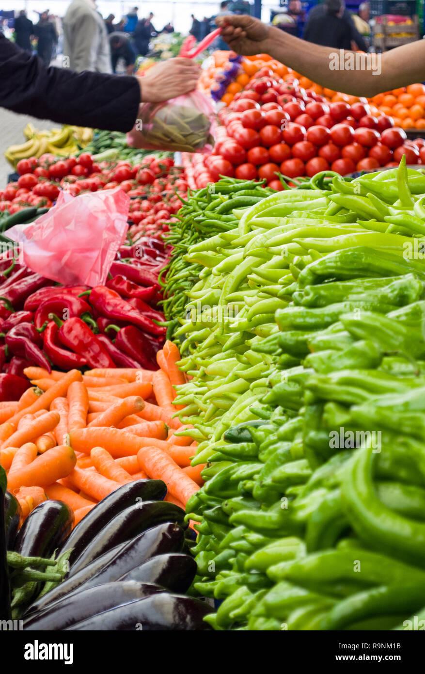 Légumes frais et biologiques sur le marché agricole. Main de l'acheteur et main du vendeur sur fond flou. Banque D'Images