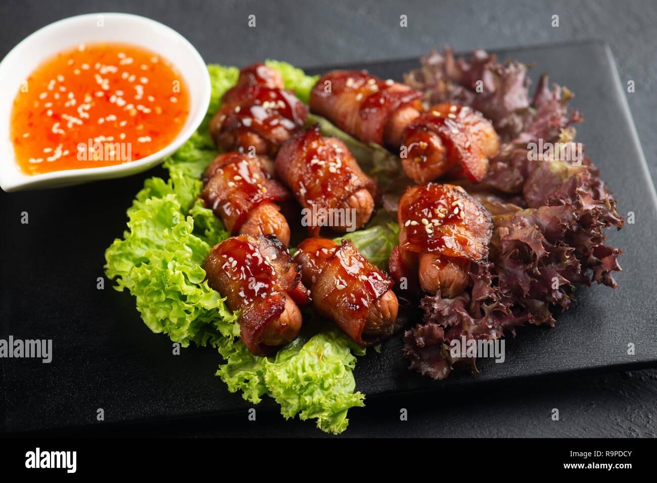 Les porcs dans des couvertures. Mini saucissons enveloppés dans du bacon fumé dans le plat de cuisson Banque D'Images