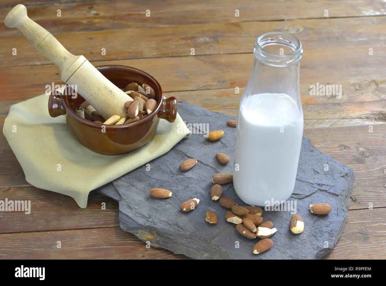 Lait d'amande fait maison en bouteille avec des amandes dans un bol. Substitut au lait lait - close up avec un espace réservé au texte Photo Stock