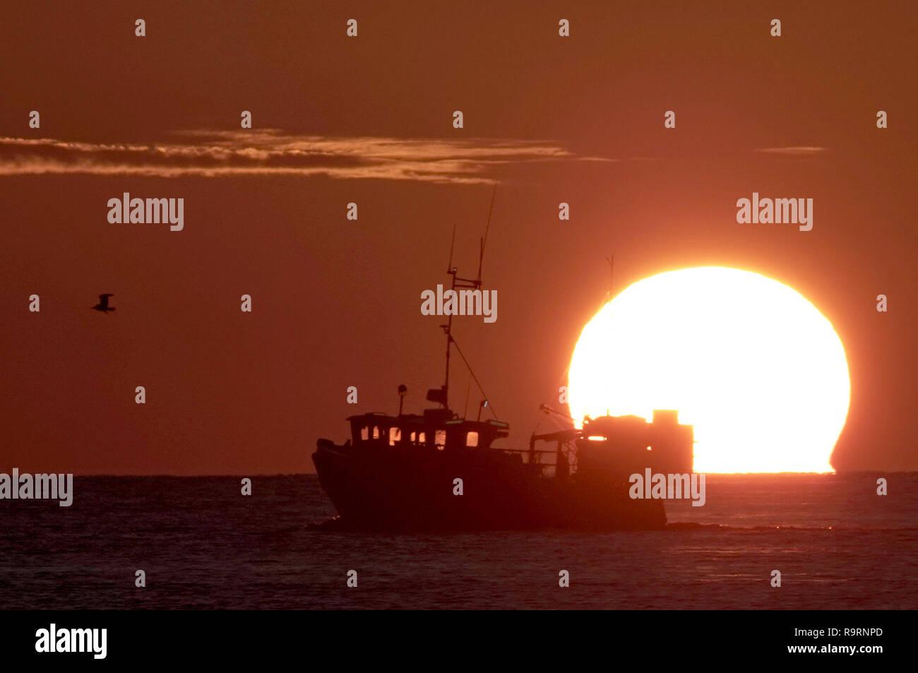 Portland, Dorset, UK. 27 Dec 2018. Météo France: bateau de pêche au coucher du soleil, Portland, Dorset Crédit: Finnbarr Webster/Alamy Live News Banque D'Images