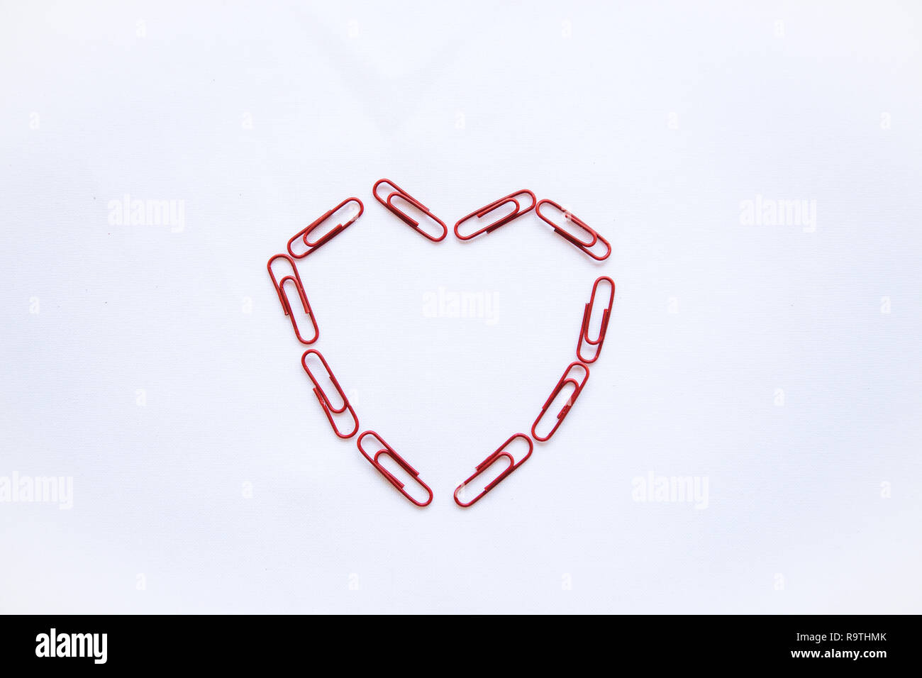Des agrafes disposées en forme de cœur sur un fond blanc. Valentine's Day celebration concept dans un style minimaliste. Photo Stock