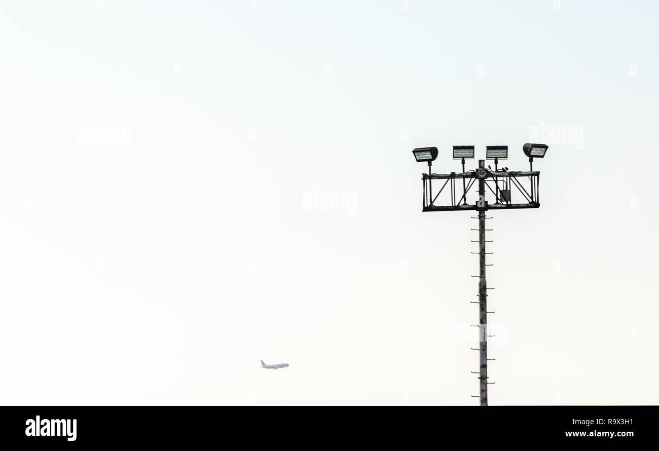 Grand pôle d'éclairage avec des lumières sur le dessus et un avion dans la distance Photo Stock