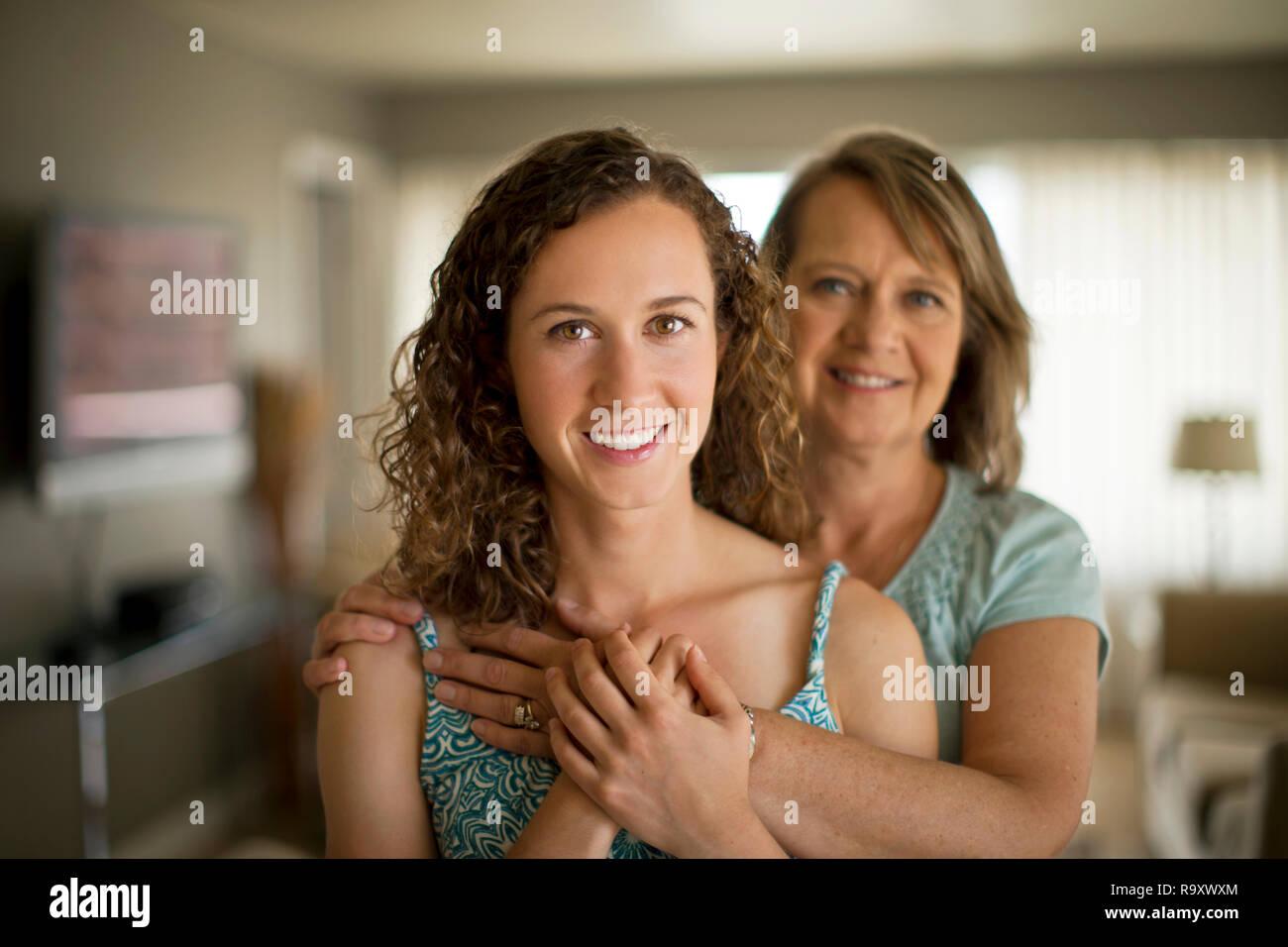 Portrait of a smiling mature woman avec ses bras autour de sa fille adulte. Photo Stock