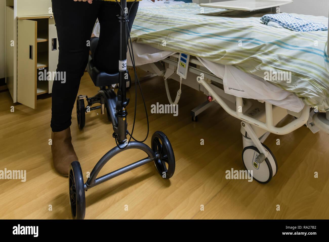 À l'aide d'un patient quitte l'hôpital DeVilbiss Healthcare d'entraînement réglable en hauteur du genou après chirurgie du pied scooter Photo Stock